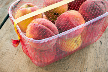 Fresh peaches in plastic bowl on wooden background