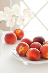 Fresh ripe peaches on a plate, selective focus