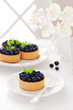 Tartlets with cream and blueberries, selective focus