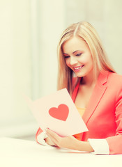 woman holding postcard with heart shape