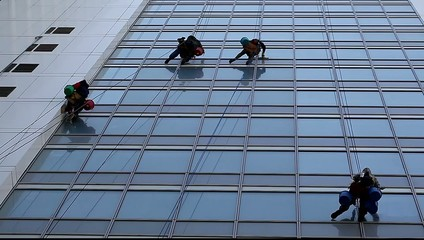 workers wash windows of high-rise buildings using the cradle
