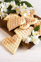 Sweet wafer hearts on dish with flowers