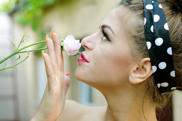 Young girl smells a roses flower