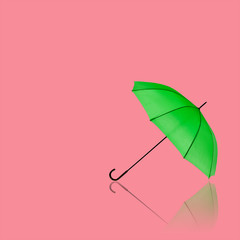 Green umbrella on pink with reflection for fashion background.