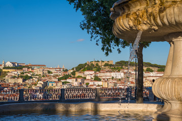 view of the city Lisbon downtown during sunset with sao jorge ca