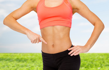 close up of woman pointing finger at her six pack
