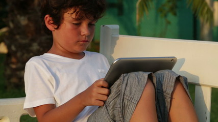Child using  digital tablet while sitting on park bench.