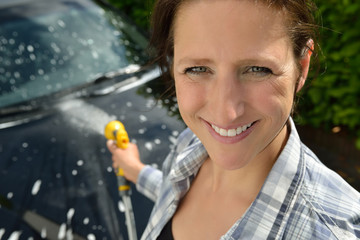 Car care - Woman using a garden spray gun to remove the soap