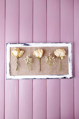Wooden frame with dried flowers on wooden background