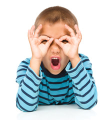 Astonished little boy is showing glasses gesture