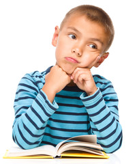 Young boy is daydreaming while reading book