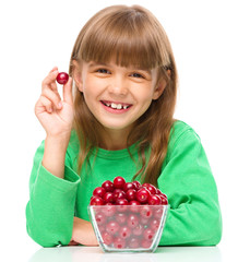 Cute girl is eating cherries