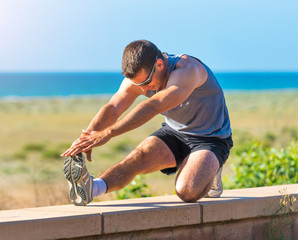 male athlete warming up before jogging