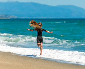 girl in a wetsuit running along the beach