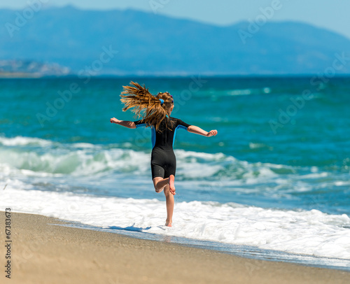 canvas print picture girl in a wetsuit running along the beach
