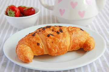 French croissant with chocolate and strawberries