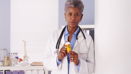 African senior doctor talking with prescription