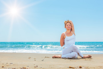 Caucasian woman practicing yoga on the beach