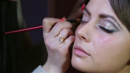 master in the beauty salon to apply makeup for eyes model