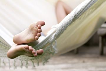 Kind met vieze voeten relaxt in hangmat