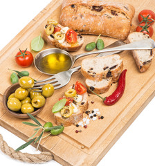 .Olive oil with green olives and bread on a wooden  board
