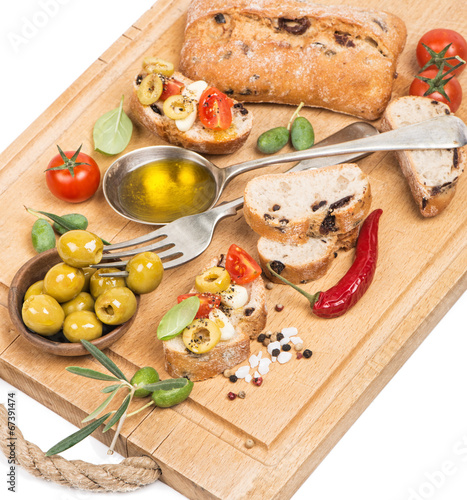 Foto op Canvas Kruiderij .Olive oil with green olives and bread on a wooden board