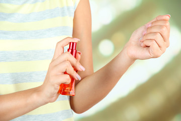 Woman testing perfume on bright background