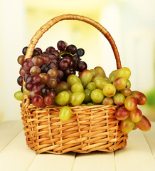 Fresh grape on wicker mat on bright background