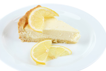 Slice of  lemon cheesecake on plate, isolated on white