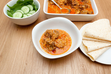 Indian curry lamb rogan josh in a white dish, with naan bread.