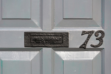 Number 73 close up on a door
