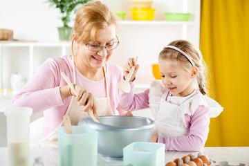 Senior woman with little girl making Dough.