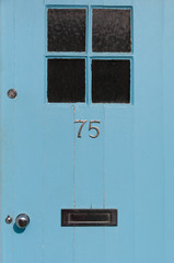 Number 75 close up on a blue door
