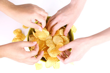 Hands of people take chips from bowl