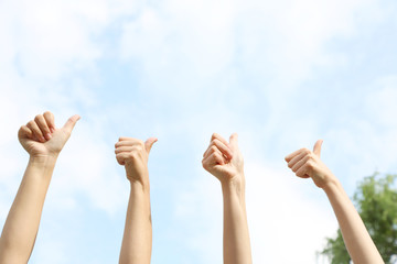 People show thumbs up on natural background
