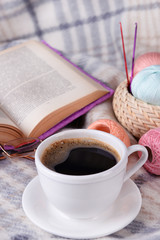 Cup of coffee and yarn for knitting on plaid with book