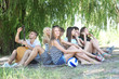 Group of friends having rest at park