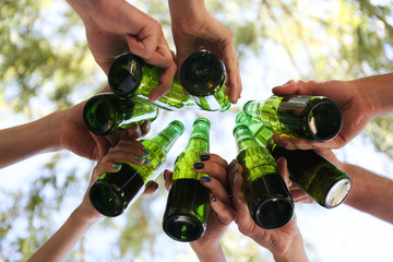 Hands holding beer bottles, close up