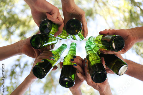 canvas print picture Hands holding beer bottles, close up