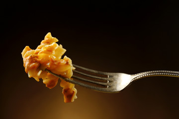Italian pasta  on fork on dark brown background