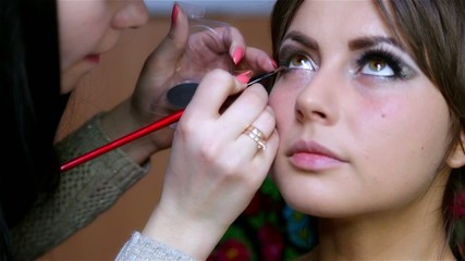 woman in a beauty salon doing eye liner, makeup