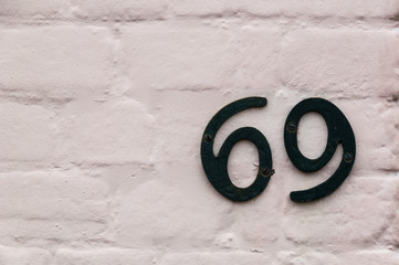 Number 69 on a white brick wall for use as a background