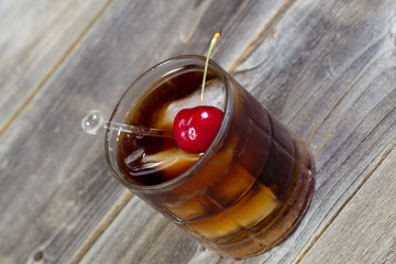 Cola and Rum with ripe cherry and ice in Glass