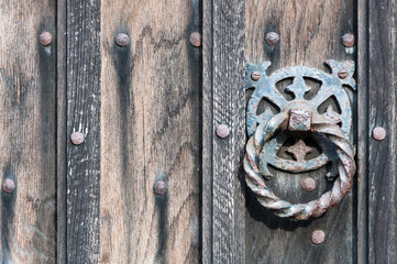 Wrought iron door knocker and wooden door close up