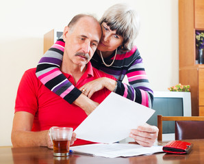 serious mature couple looking financial document