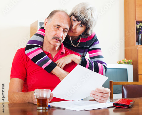 canvas print picture serious mature couple looking financial document