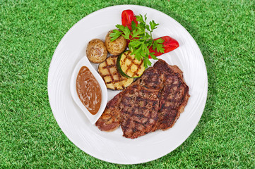 Grilled steak, baked potatoes and vegetables on white plate on g