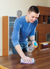 man cleaning  table with rag and cleanser
