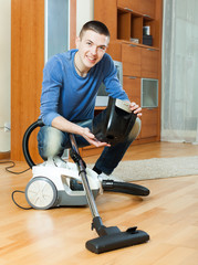 guy vacuuming with vacuum cleaner on parquet floor in living roo
