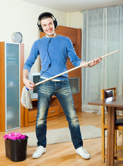 Happy man cleaning his house with mop